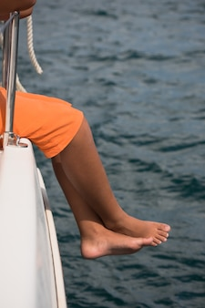 Jovem rapaz sentado ao lado de um iate. a jornada através do oceano Foto Premium