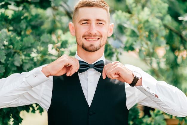 Jovem rapaz sorri e ajusta a gravata