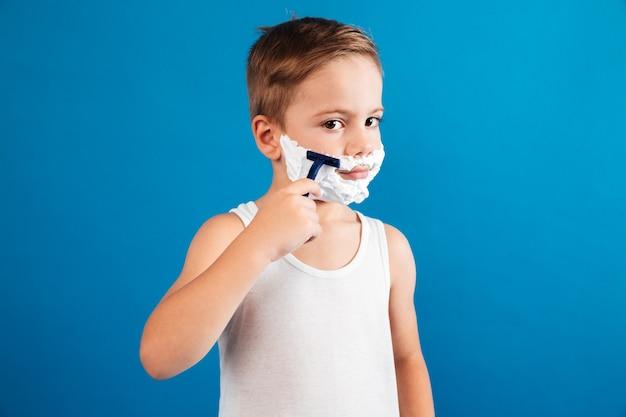 Jovem rapaz tentando raspar o rosto como homem