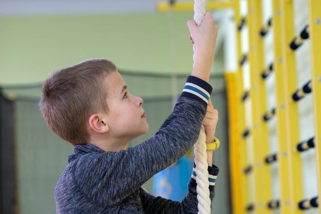 Jovem rapaz tentando subir em uma corda