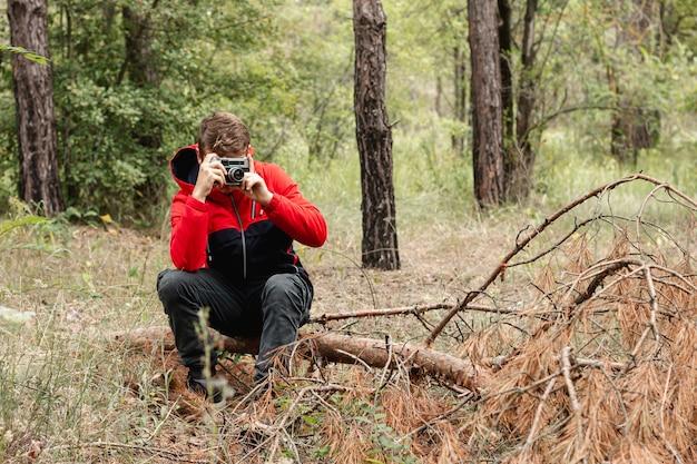Jovem rapaz tirando fotos na floresta com cópia-espaço