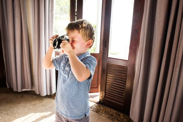 Jovem rapaz tirar fotos com a câmera de filme vintage