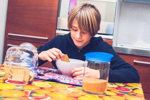 Jovem rapaz tomando café da manhã antes de ir para a escola novo dia da vida comum