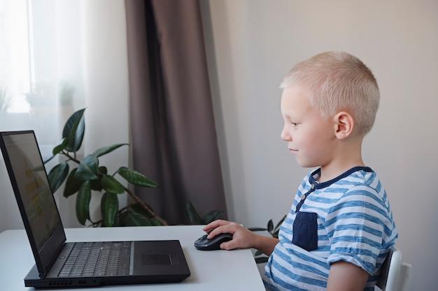 Jovem rapaz trabalhando em um computador em casa. e-aulas para crianças.