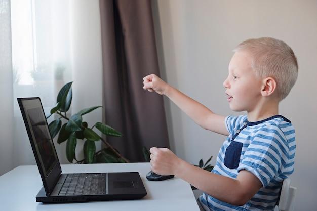 Jovem rapaz trabalhando ou jogando em um computador em casa. e-aulas para crianças.