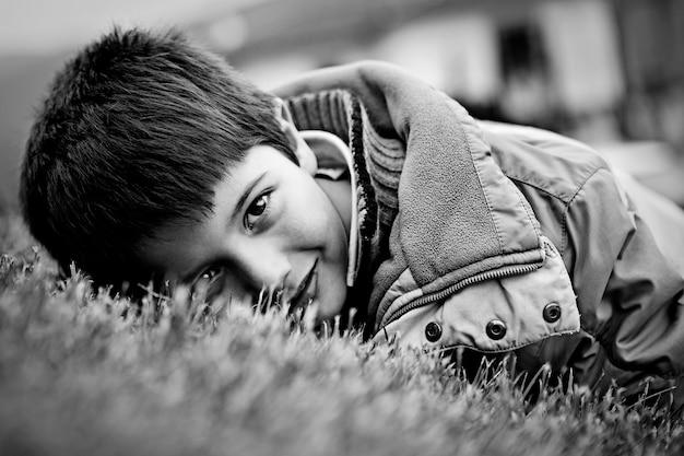 Jovem rapaz tranquilo no casaco deitado na grama sonhando