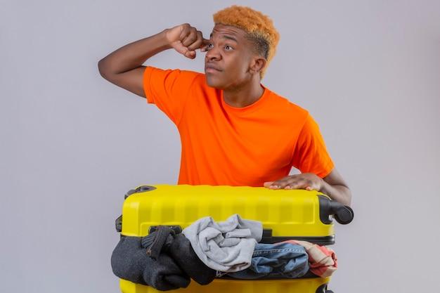 Jovem rapaz vestindo uma camiseta laranja em pé com uma mala de viagem cheia de roupas olhando para o lado com uma expressão pensativa no rosto pensando sobre a parede branca