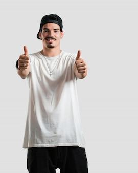 Jovem rapper homem alegre e animado, sorrindo e levantando o polegar para cima