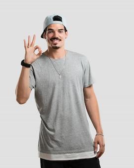 Jovem rapper homem alegre e confiante fazendo gesto de ok, animado e gritando