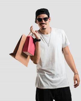 Jovem, rapper, homem, alegre, e, sorrindo, muito, excitado, carregar, um, bolsas para compras