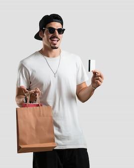 Jovem, rapper, homem, alegre, e, sorrindo, muito, excitado, segurando, a, novo, cartão banco, e, bolsas para compras, pronto, ir, shopping
