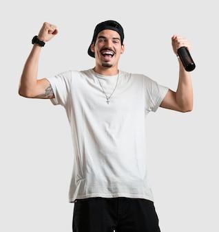 Jovem rapper homem feliz e divertido, segurando uma garrafa de cerveja, se sente bem depois de um dia intenso