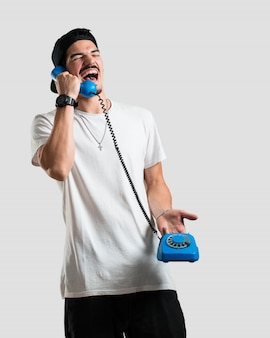 Jovem rapper homem rindo alto, se divertindo com a conversa, chamando um amigo ou um cliente