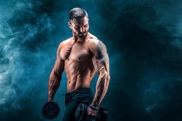 Jovem rasgou o fisiculturista de homem com abs perfeito, ombros, bíceps, tríceps e peito, posando com um haltere
