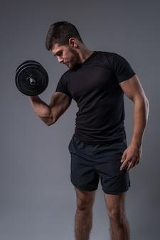 Jovem realizando uma rosca direta de bíceps com halteres