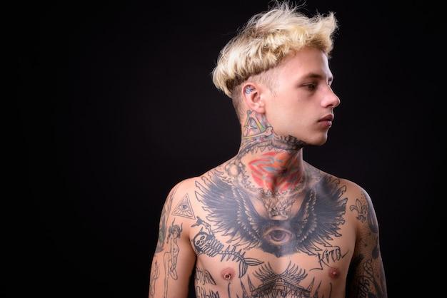 Jovem rebelde bonito com tatuagens sem camisa