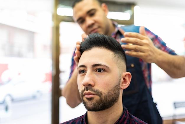 Jovem recebendo um penteado em um barbeiro.