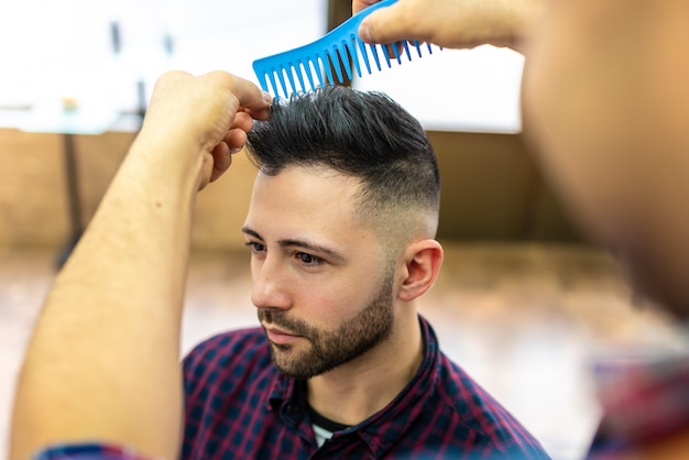 Jovem, recebendo um penteado em uma barbearia