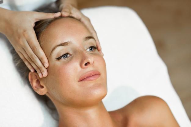 Jovem recebendo uma massagem na cabeça em um centro de spa.