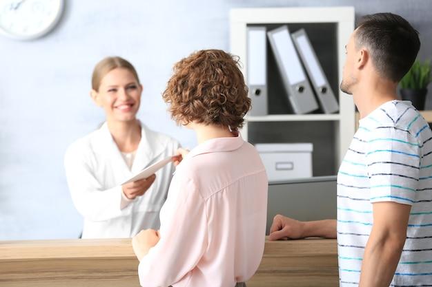 Jovem recepcionista com clientes no hospital