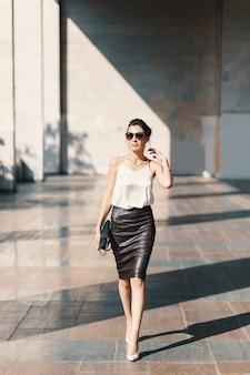 Jovem refinada em saia de couro e blusa de seda andando confiante perto de um edifício.