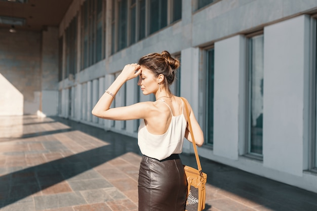 Jovem refinada em saia de couro e blusa de seda, pensando em como resolver uma situação.