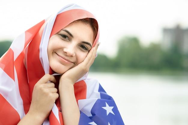 Jovem refugiada feliz com a bandeira nacional dos eua na cabeça e ombros