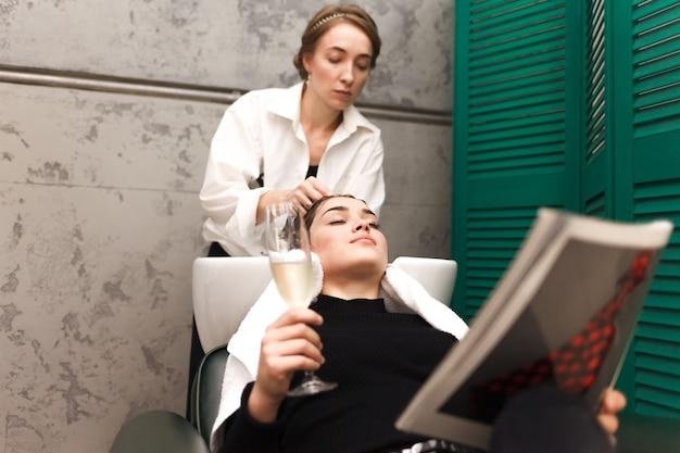 Jovem relaxa em um salão de beleza com uma taça de champanhe enquanto lava o cabelo