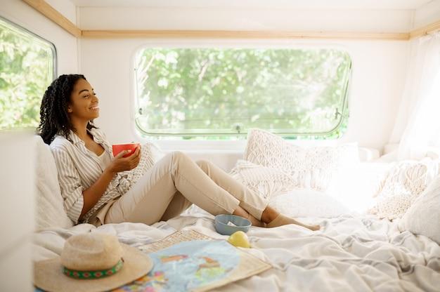 Jovem relaxa na cama, acampando em um trailer. casal viaja em van, férias em autocaravana, lazer em autocaravana