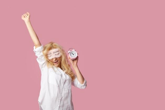 Jovem relaxada de pijama e máscaras de dormir em uma parede rosa. despertador acordou a menina