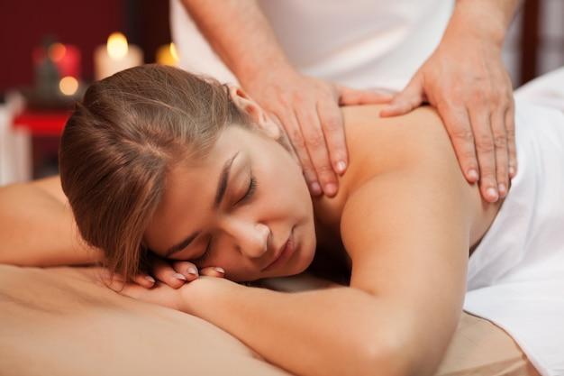 Jovem relaxada desfrutando de massagem relaxante nas mãos do massagista qualificado. terapeuta de spa trabalhando com sua cliente do sexo feminino, massageando as costas no centro de beleza. serenidade, harmonia, prazer