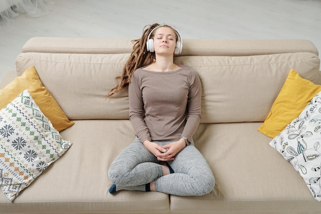 Jovem relaxada em roupas esportivas, sentada no sofá e ouvindo música tranquila em fones de ouvido