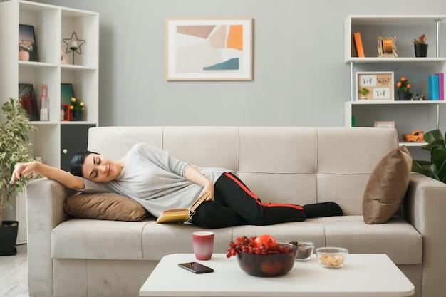Jovem relaxada lendo um livro deitado no sofá atrás da mesa de centro na sala de estar