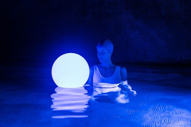 Jovem relaxada na piscina com luz neon