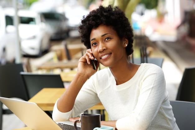 Jovem relaxada no café falando no celular