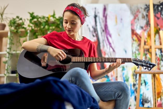 Jovem relaxada tocando violão, aprendendo a tocar sentada na cama com roupas casuais em