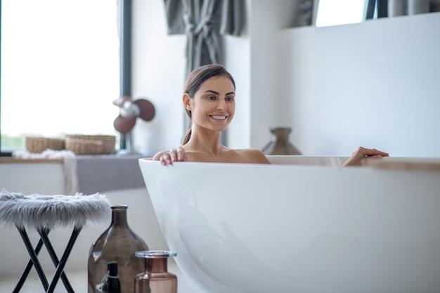 Jovem relaxada tomando banho em casa