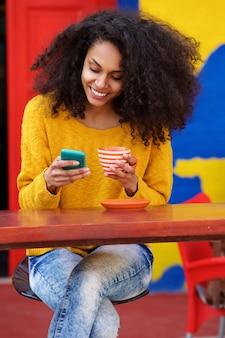 Jovem relaxada usando telefone celular na cafeteria