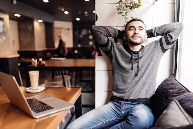 Jovem relaxado com as mãos atrás da cabeça e sorrindo enquanto está sentado à mesa com o laptop em um café moderno