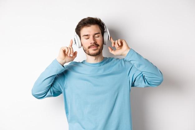 Jovem relaxado curtindo a música favorita, ouvindo música em fones de ouvido com os olhos fechados e rosto calmo, em pé sobre um fundo branco.