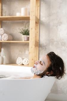 Jovem relaxado usando máscara facial enquanto está deitado na banheira com água quente e espuma no espaço da prateleira com itens para amor próprio