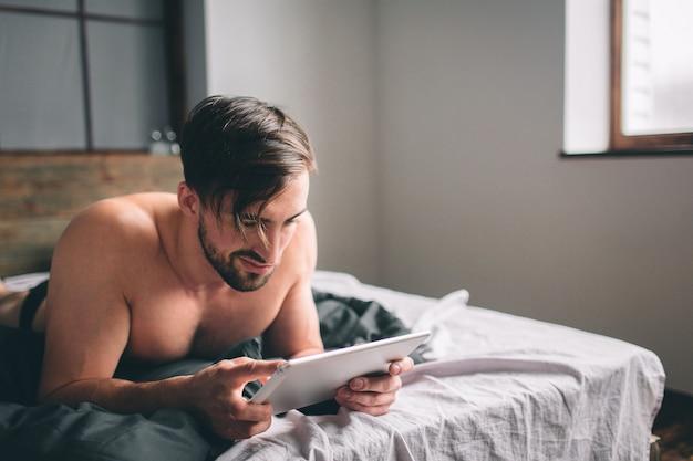 Jovem relaxamento na cama e usando tablet digital