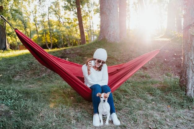 Jovem relaxando com o cachorro na rede
