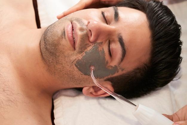 Jovem relaxando com os olhos fechados enquanto cosmetologista aplica máscara de argila e faz procedimento de limpeza por ultrassom com dispositivo especial