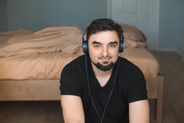 Jovem relaxando e sorrindo com fones de ouvido, ouvindo música em casa