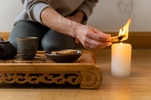 Jovem relaxando em casa com chá e velas