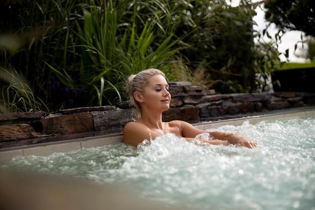 Jovem relaxando em uma banheira de hidromassagem