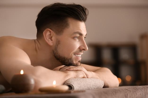 Jovem relaxando na mesa de massagem em salão de spa