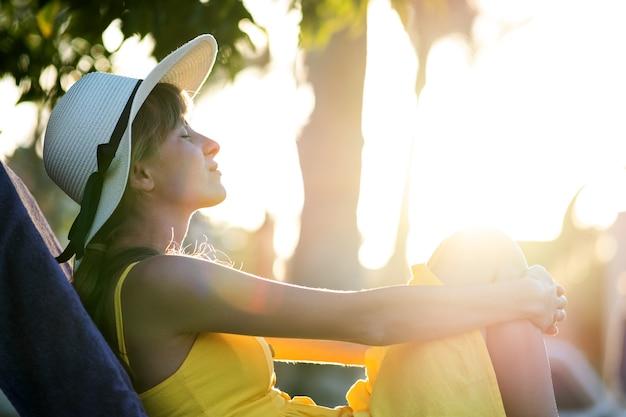 Jovem relaxante ao ar livre em um dia ensolarado de verão. senhora feliz deitada na cadeira de praia confortável, sonhando pensando acordado. calma linda garota sorridente, aproveitando o ar fresco e relaxando com os olhos fechados.