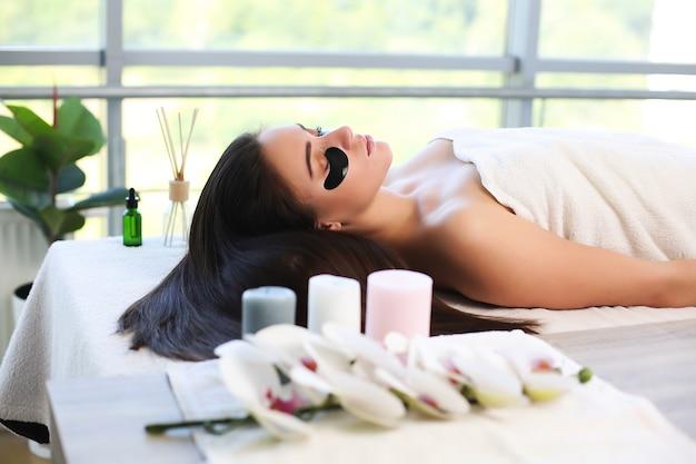 Jovem relaxante durante a tradicional massagem tailandesa no spa e centro de bem-estar.